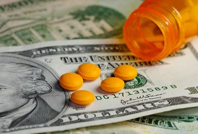 Orange pills laying on money