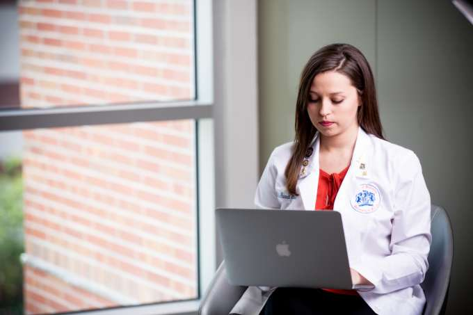 Image of student in white coat on laptop