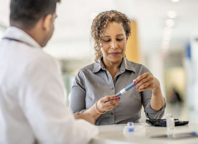 Woman holding diabetes device with doctor